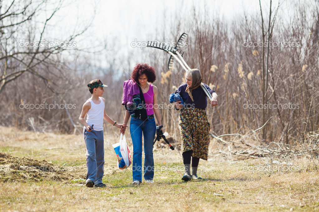 Son, mother and grandmother returning home from work in the field, talking on the way — Stock Photo #9883336