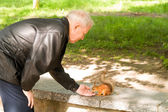 Man and squirrel — Stock Photo