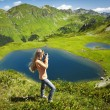 Beautiful young woman with red hair standing on rock, and photog — Stock Photo