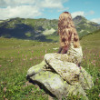 Beautiful young woman in mountains on a meadow — Stock Photo