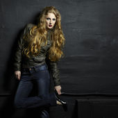 Portrait of a young redheaded woman in a leather jacket — Stock Photo