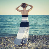 Beautiful young woman standing on the beach — Stock Photo