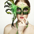 The beautiful young woman in a green mysterious venetian mask — Stock Photo