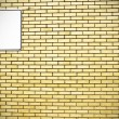 Yellow brick wall and white sign — Stock Photo #9368966
