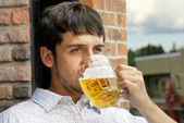 Young guy drinking beer — Stock Photo