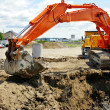 Orange mechanical digger and hole - Stock Photo