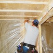 Man putting vapor barrier in house — Foto Stock