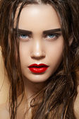 Hot young woman model with sexy bright red lips makeup, strong eyebrows, clean shiny skin and wet hairstyle. Beautiful fashion portrait of glamour female face — Stock Photo