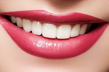Close-up happy female smile with healthy white teeth, bright magenta lips make-up. Cosmetology, dentistry and beauty care. Macro of woman's smiling mouth