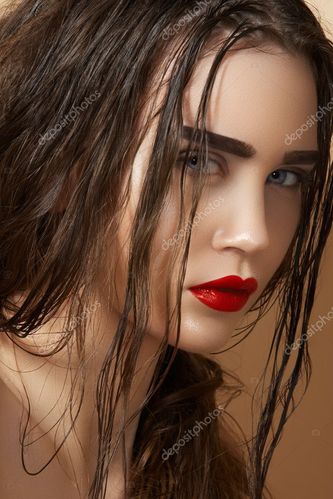Hot young woman model with sexy bright red lips makeup, strong eyebrows, ...