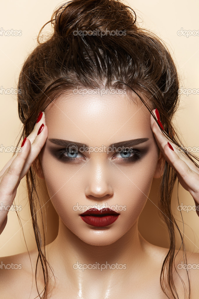 Hot young woman model with sexy dark red lips makeup, strong eyebrows, clean shiny skin and wet bun hairstyle. Beautiful fashion portrait of glamour female face. — Stock Photo #9224157