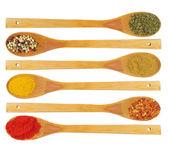 Varias especias en cucharas de madera aisladas — Foto de Stock