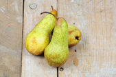 Three pears on wooden background — Stock Photo