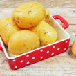 Raw potatoes in red tray - Photo
