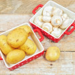 Raw mushrooms and potatoes in red trays - Stockfoto