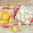 Raw mushrooms and potatoes in red trays — Stock fotografie