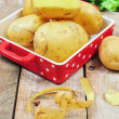 Raw potatoes in red tray and potato peels - Stockfoto