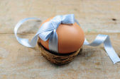 Natural easter egg with blue ribbon in nest — Stock Photo