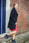 Mladá žena chodí dveřmi — Stock fotografie