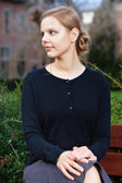 Pretty young blond woman sitting on bench — Stock Photo