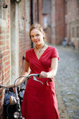 Pretty young woman with bicycle — Stock Photo