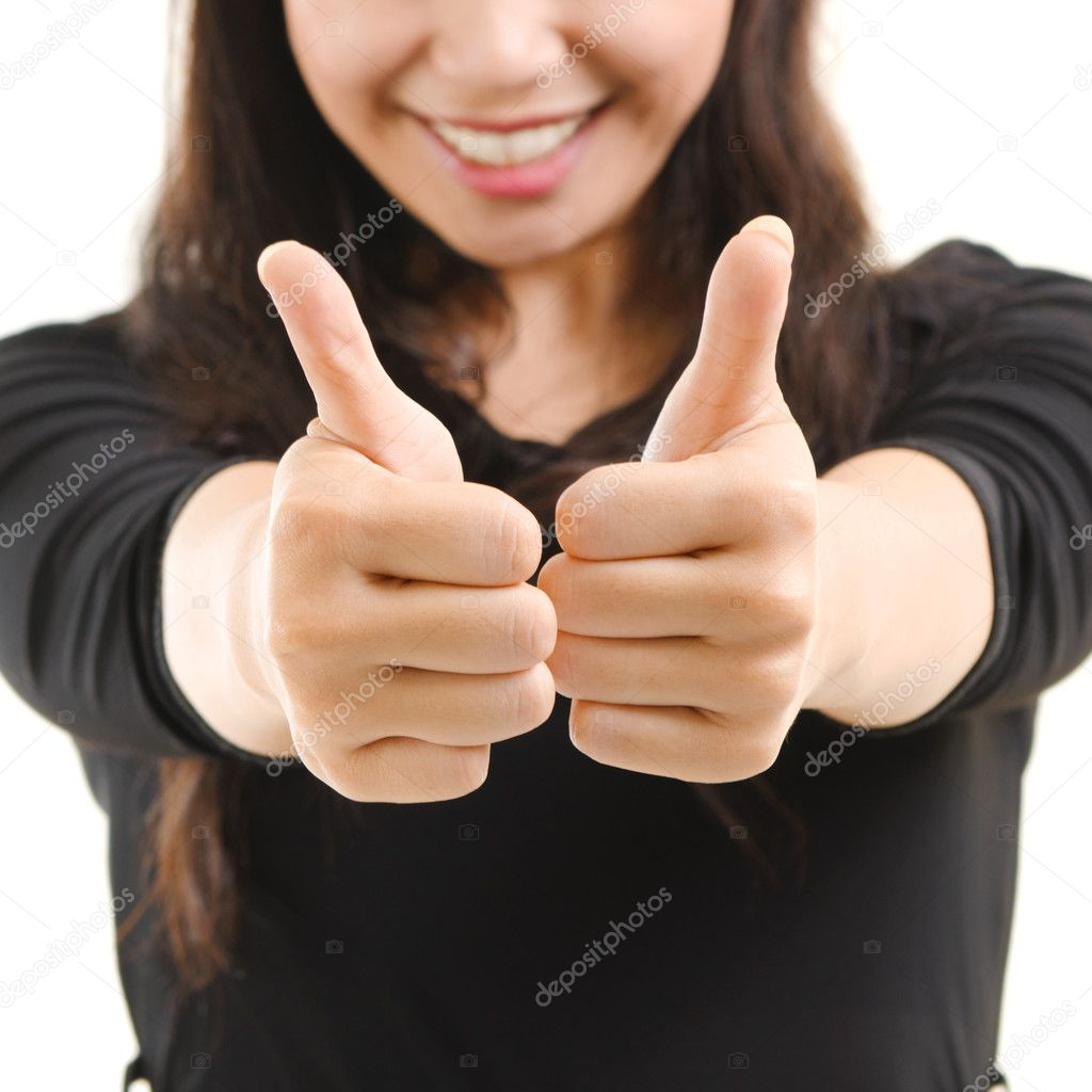 Young Asian female giving thumbs up sign isolated on white background  Stock Photo #10664220