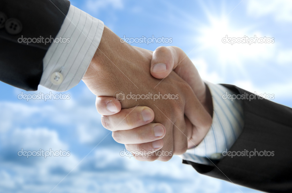 Businessmen shaking hands over blue sky, low angle view. — Stock Photo #9235043