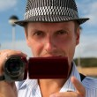 Man in a hat with a camera — Stock Photo