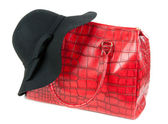 Red Fashion ladies handbag and a black felt hat — Stock Photo