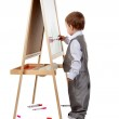 A child paints on an easel in the studio — Stock Photo