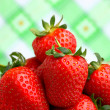 Delicious strawberries on spring green background — Stock Photo