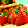 Delicious strawberries in wicker brown basket — Stock Photo