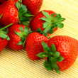 Delicious strawberries on bamboo mat background — Stock Photo