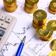 Money coins, calculator on the business stock charts - Stock Photo