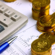 Money coins, calculator on the businness stock charts - Lizenzfreies Foto