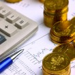 Money coins, calculator on the businness stock charts - Stock Photo