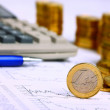 Money coins, calculator on the businness stock charts — Stock Photo