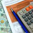 Stock Photo: The tax form with calculator, money and pen