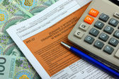 The tax form with calculator, money and pen — Stock Photo