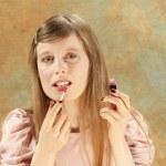 Blonde putting lipstick — Stock Photo