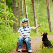 The boy with his dog in the forest — Stock Photo