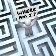 Where Am I Person Holding Sign Lost in Maze - Stock Photo