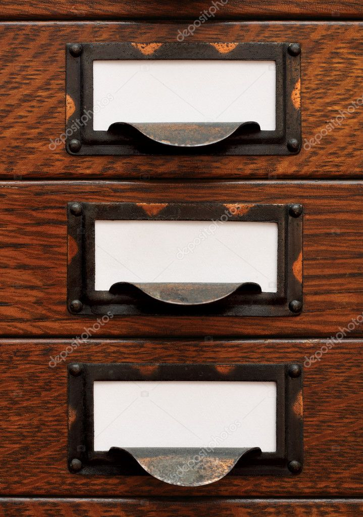 Vertical stack of three small, old oak flat file drawers with white empty tags in tarnished brass label holders. — Stock Photo #10502254
