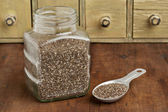 Jar and tablespoon of chia seeds — Stock Photo