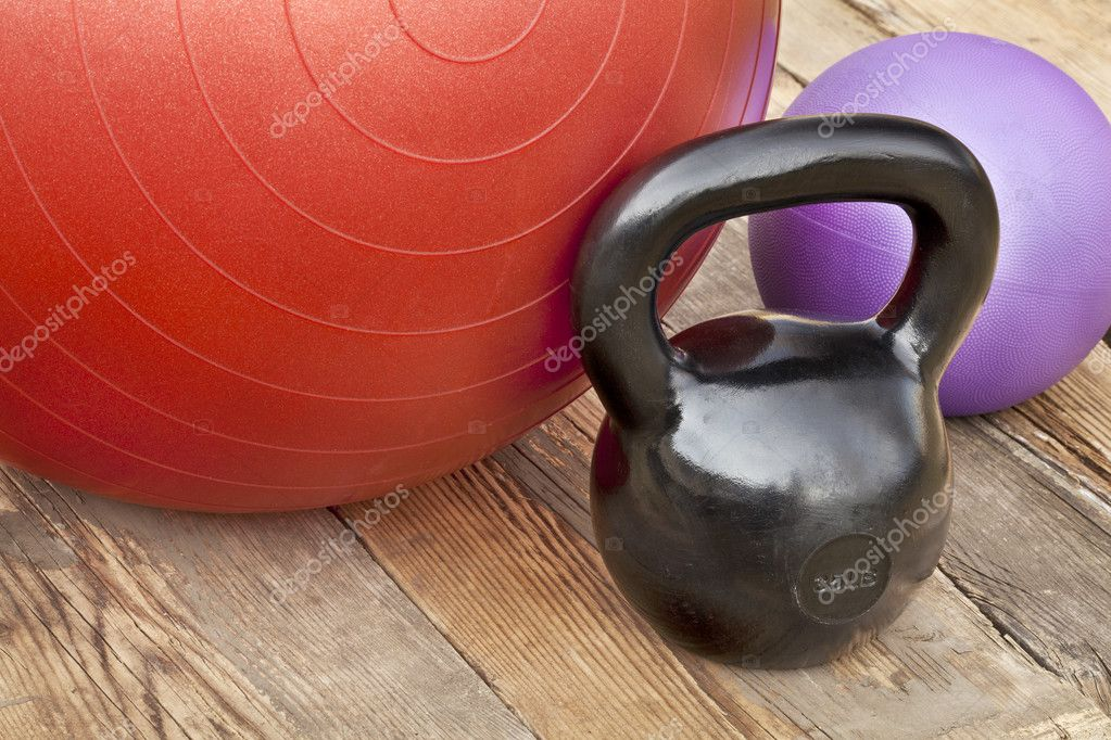 Black iron kettlebell, Swiss and medicine exercise balls on wooden deck - fitness concept — Stock Photo #8872746
