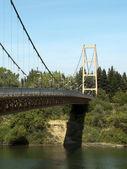 Suspension walking bridge spanning river blue sky — Stock Photo