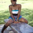 Attractive young black woman straddling park bench — Stock Photo #8310580