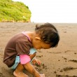 Asian toddler girl writing on beach sand — ストック写真