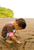 Asian toddler girl writing on beach sand — Stock Photo