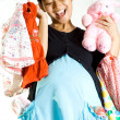 Happy pregnant woman with baby clothing and bunny doll — Stock Photo